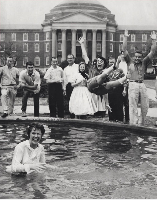 Girl getting thrown in fountain, ca. 1950s