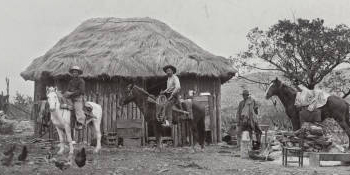 Cowboys in front of small house with thatch roof on ranch, ca. 1900